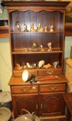 A REPRODUCTION OAK FINISHED DRESSER TYPE UNIT, having plate rack back, with two inline drawers,