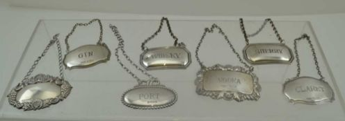 A COLLECTION OF SEVEN ASSORTED SILVER WINE & SPIRIT LABELS, various stamped shapes, with chains,