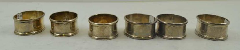 A SET OF SIX SILVER NAPKIN RINGS of plain oval form, combined weight; 114g