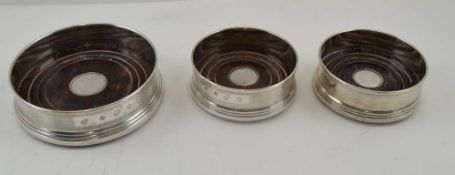 W.I. BROADWAY & CO. THREE SILVER GALLERY BOTTLE COASTERS, turned wood bases, engine turned