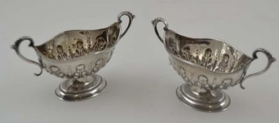NATHAN & HAYES A PAIR OF SILVER SALTS, boat form with two handles, repousse decoration on oval