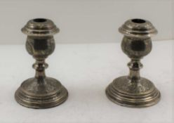A PAIR OF PERSIAN SILVER CANDLESTICKS, overall chased decoration, bear various stamped marks, c.