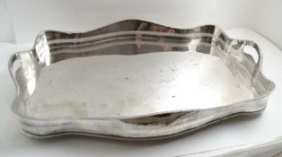 A SILVER PLATED SERPENTINE GALLERY TEA TRAY, two pierced handles in the gadrooned gallery, 61.5cm