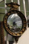A REGENCY DESIGN GILT FRAMED CONVEX WALL MIRROR with ball frame and eagle crest, plate size; 28cm