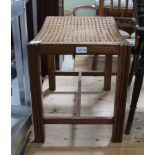 A RECTANGULAR BERGERE TOPPED STOOL on pilaster style legs, united by an 'H' shaped stretcher
