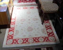 A WOVEN WOOLED PAKISTANI FLOOR RUG with pale central field & red floral design guard border, 178cm x