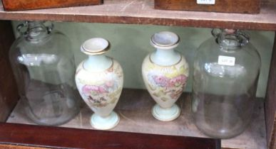 TWO GLASS DEMI JOHNS together with a pair of floral decorated pottery vases in the manor of Doulton