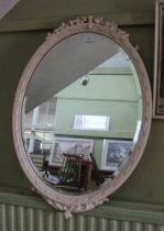 A LATER WHITE PAINTED FANCY FRAMED OVAL BEVEL PLATE WALL MIRROR
