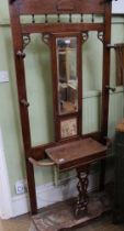 AN EARLY 20TH CENTURY OAK HALL STAND with central bevelled mirror plate, over probable Minton