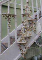 FOUR VARIOUS WALL BRACKETS, currently painted cream and highlighted in gilt, with Rococo scrolling