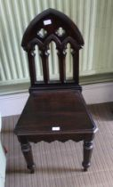A LATE 19TH / EARLY 20TH CENTURY HALL CHAIR with ecclesiastical gothic design back over solid seat