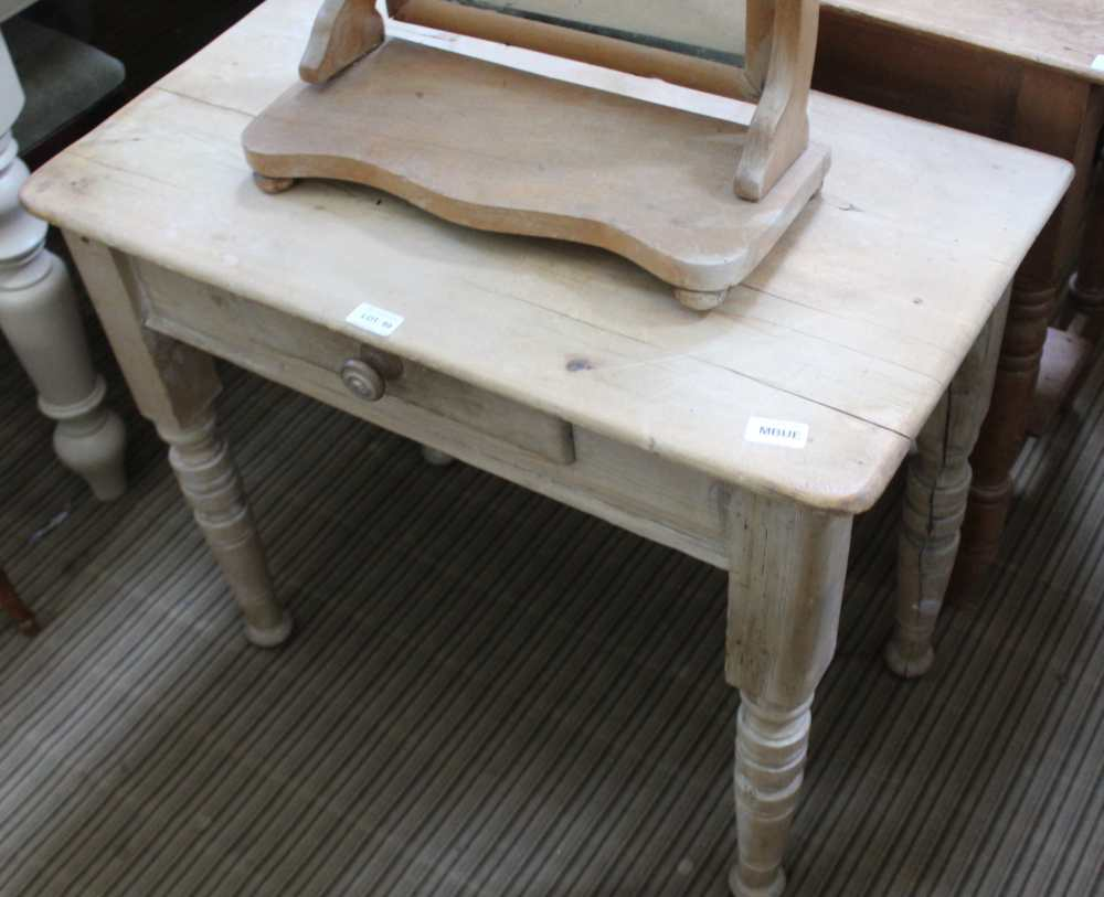 A LOW PINE SIDE TABLE fitted with a single central drawer, supported on short turned legs