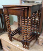 AN OAK NEST OF THREE TABLES the smallest having concealed drawers, on bobbin turned legs