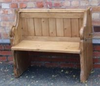 A 19TH CENTURY PINE FORMED TWO-SEATER PEW / SETTLE, having prayer book shelved back, on shaped plank