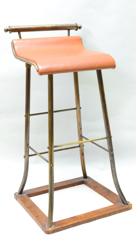 AN EARLY TO MID 20TH CENTURY COUNTER STOOL, brass frame with a sweeping seat on an oak frame base,