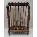 A WOODEN CROQUET SET ON STAND comprising seven mallets, six balls, two posts & five iron hoops,
