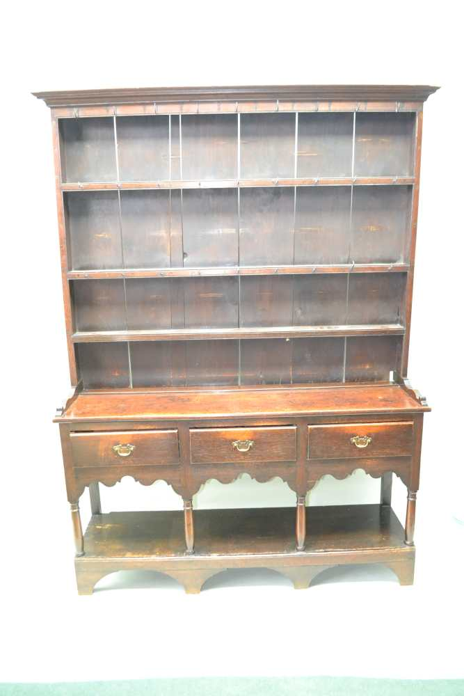 A LATE GEORGE III OAK DRESSER, the base fitted three drawers, with brass handles over shaped aprons,