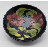 A MOORCROFT POTTERY LOW TAZZA, the bowl tube lined and painted hibiscus pattern on a cobalt blue