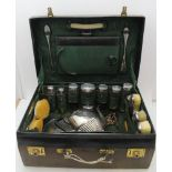 AN EARLY 20TH CENTURY GREEN LEATHER VANITY CASE, silver fitted, London 1912, contains eight