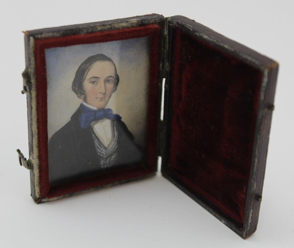A MID 19TH CENTURY MINIATURE PORTRAIT PAINTING, a young gentleman wearing a blue bow tie,