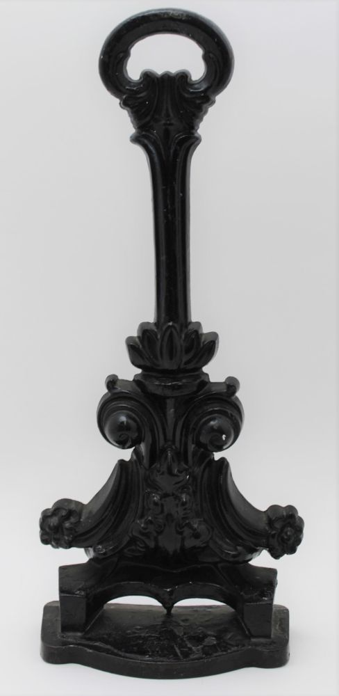 A LATE VICTORIAN CAST IRON DOOR PORTER, of acanthus scroll design, ebonised finish, 39.5cm high