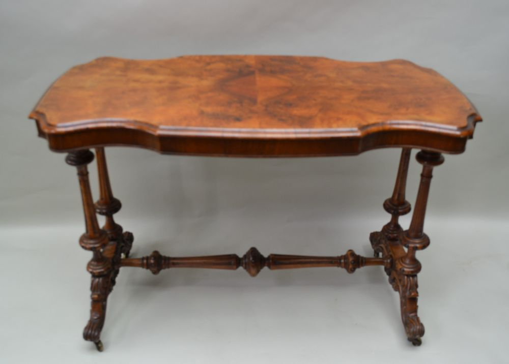 A 19TH CENTURY WALNUT FANCY SHAPED CENTRE TABLE having quarter veneered top, supported on four