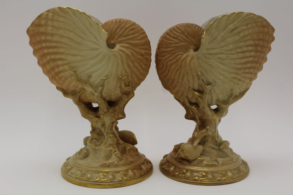 A PAIR OF ROYAL WORCESTER PORCELAIN NAUTILUS SHELL VASES, raised on coral moulded stems and shell