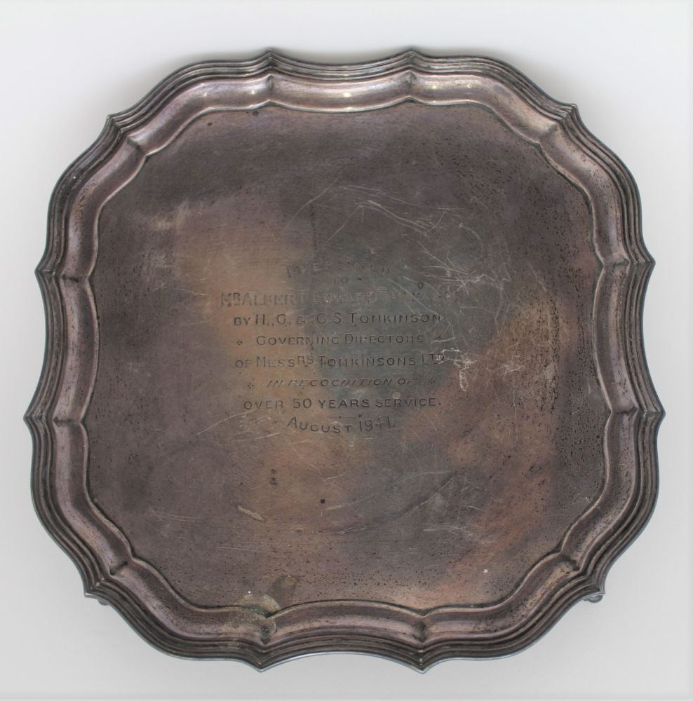 BARKER BROTHERS SILVER LTD, A SILVER PIECRUST SALVER, of square form, raised on four supports,