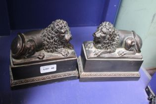 A PAIR OF PATINATED CAST RESIN RECUMBENT LIONS on plinth
