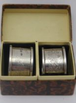 JOSEPH GLOSTER LTD A pair of silver napkin rings, floral chased decoration, Birmingham 1913, in a
