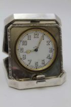 GOLDSMITHS & SIVERSMITH CO. LTD, A SILVER CASED TRAVEL CLOCK, hinged form with bounds reed edge,