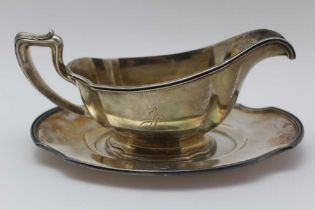 A STERLING SILVER SAUCE BOAT with stand, considered to be Gorham, Georgian design, monogrammed, 522g