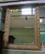 A LARGE RECTANGULAR BEVEL PLATE WALL MIRROR in fancy gilt frame, with leaf and berry pattern