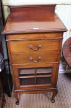A MAHOGANY FINISHED MUSIC CABINET with two drawers over bar glazed cupboard door, supported on short