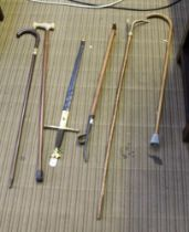 A SELECTION OF WALKING STICKS and associated items, to include a weed dibber