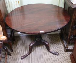 A 19TH CENTURY MAHOGANY CIRCULAR TILT TOP TABLE on turned column and three outswept legs