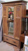 AN ART NOUVEAU DESIGN OAK WARDROBE having single insert bevelled mirror door over full width shoe