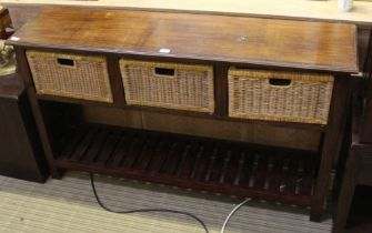 A MAHOGANY FINISHED IMPORTED HARDWOOD SIDE UNIT, having three inline woven bamboo drawers, supported