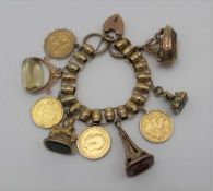 A YELLOW METAL CHARM BRACELET set with four framed full sovereigns, and five fob seals, some
