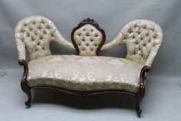 A VICTORIAN WALNUT SHOW WOOD FRAMED CONVERSATION SETTEE, having carved shield shaped back central