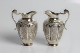 A pair of unmarked white metal jugs with decorative design on eight panelled body, 11cm x 7.5cm x