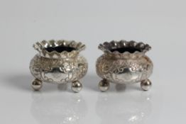 A pair of Victorian silver salts with blue glass liners on three ball feet, decorated with floral