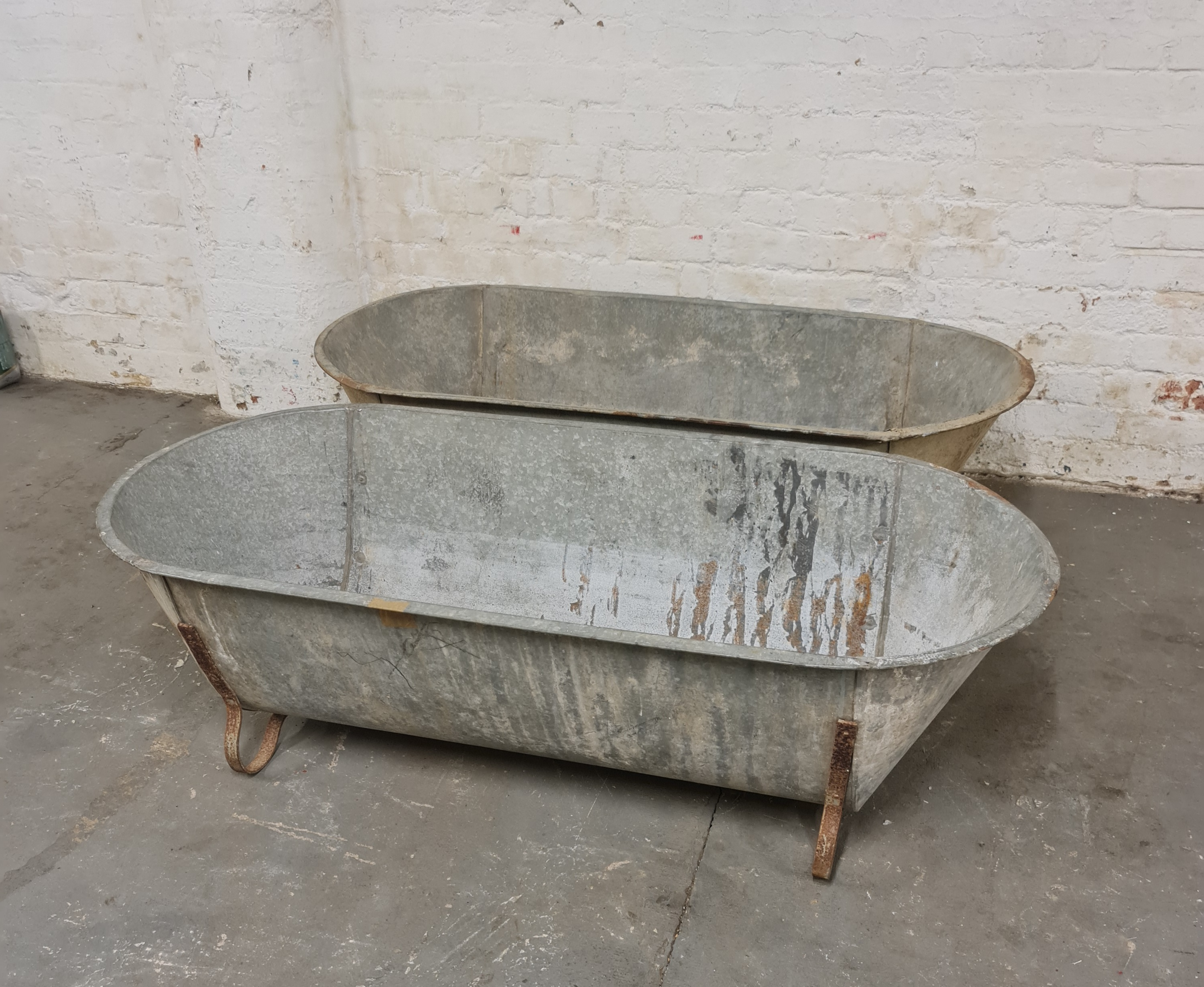 Two large galvanised feeding troughs.