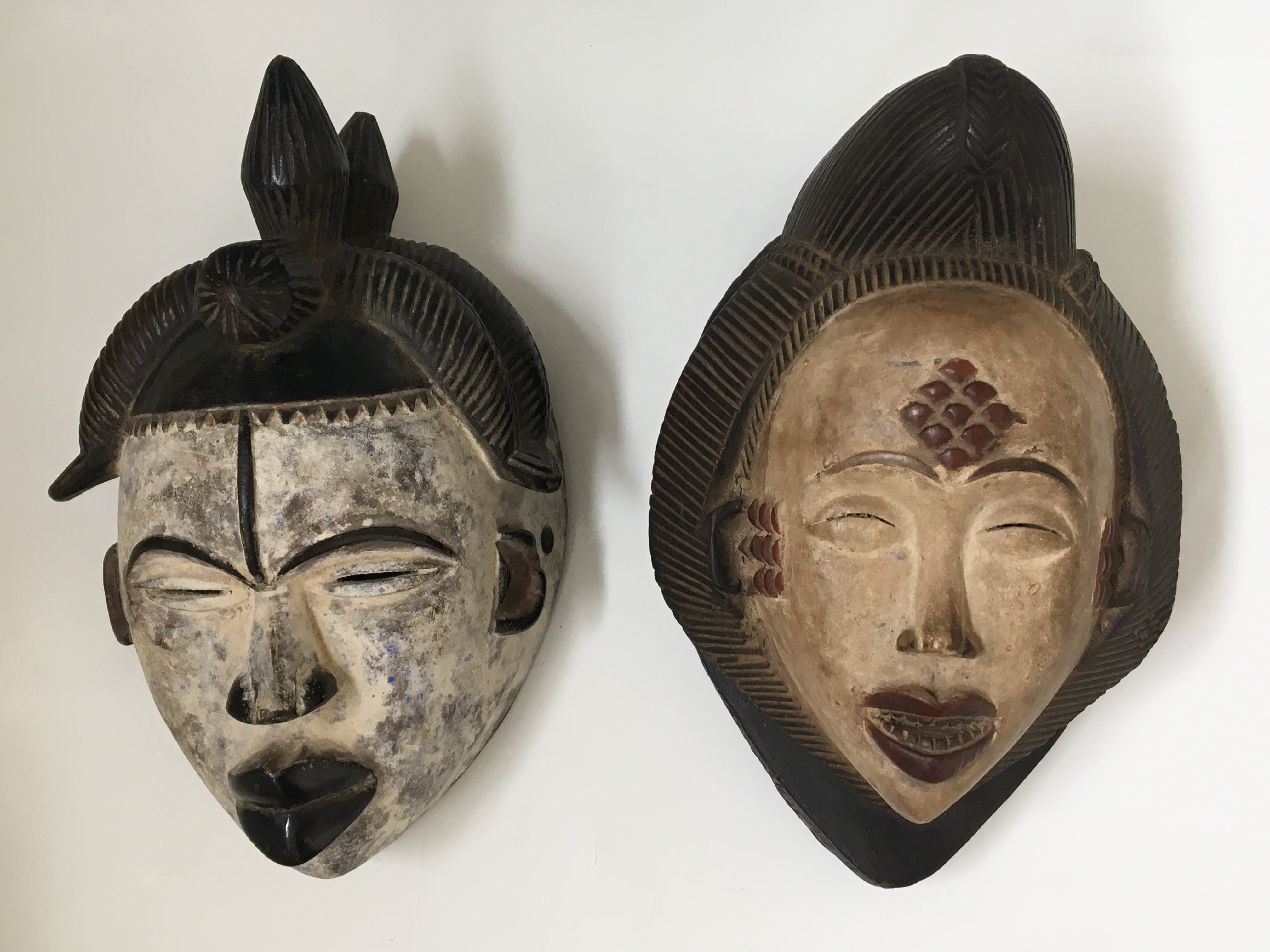 Two West African tribal face masks, with carved hair details. IMPORTANT: Online viewing and