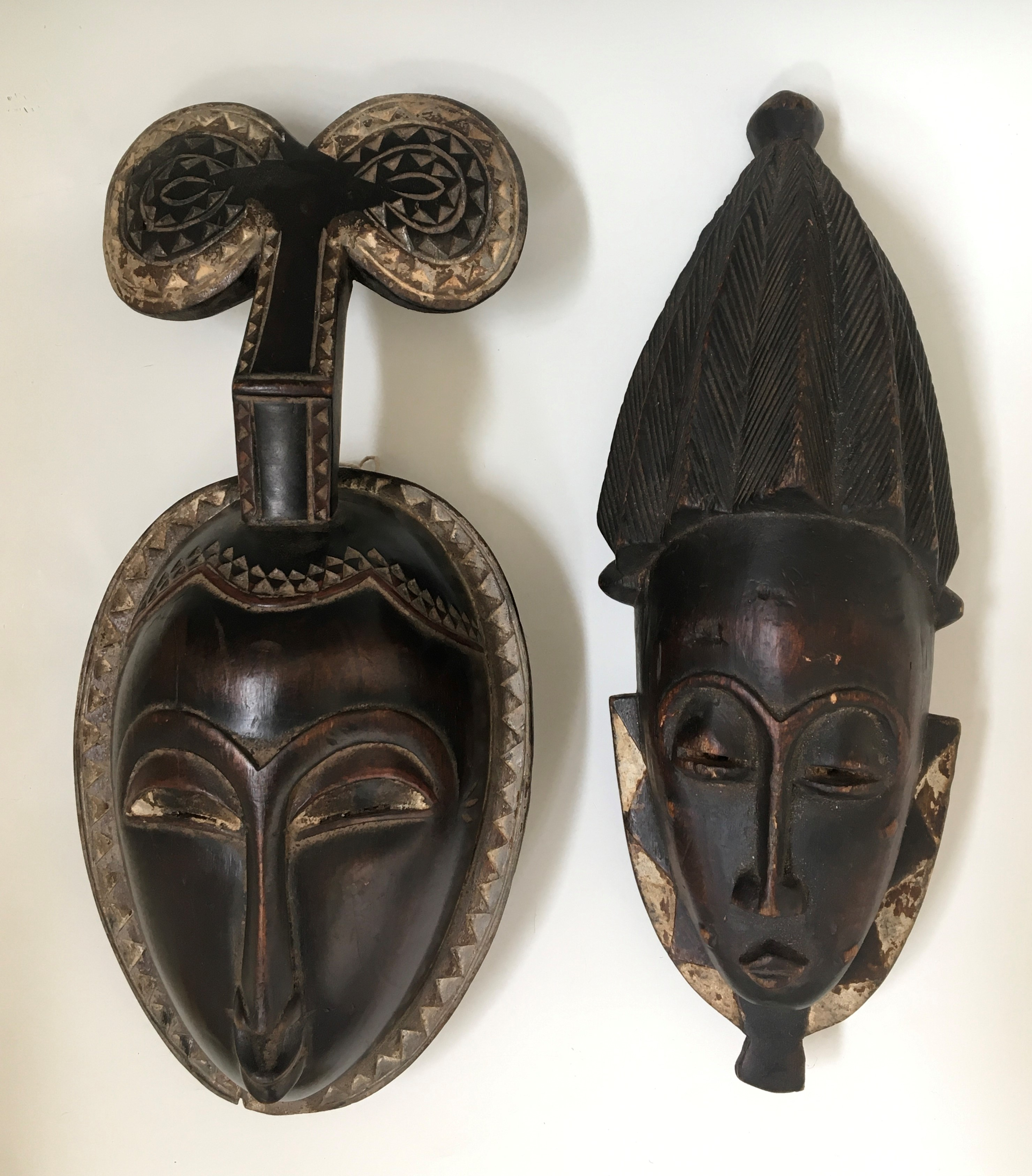 Two West African tribal face masks, with diamond borders and traces of white painted detail.