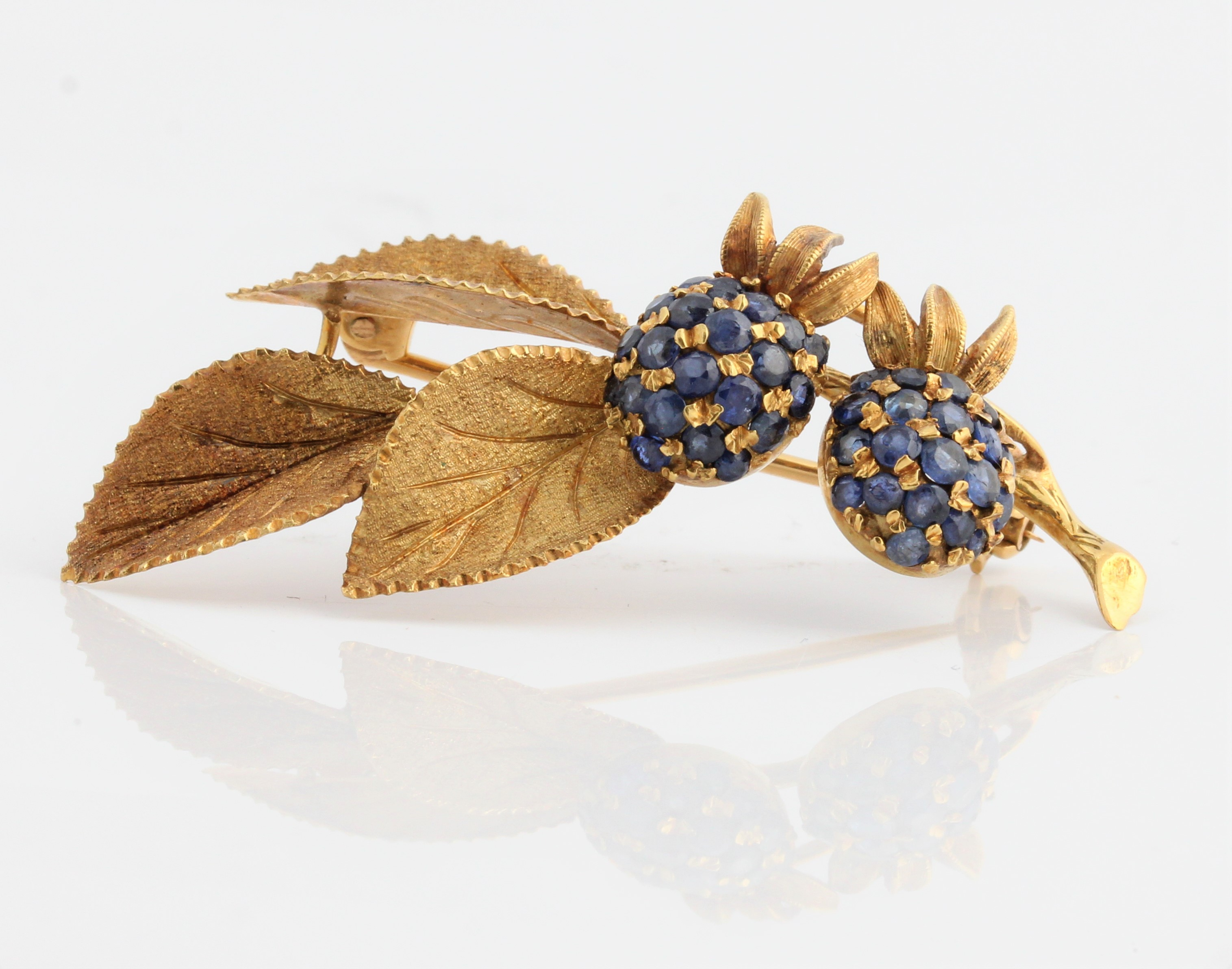 A sapphire set berry and leaf design brooch, stamped 750, length approx. 5cm weight approx. 8.6g.