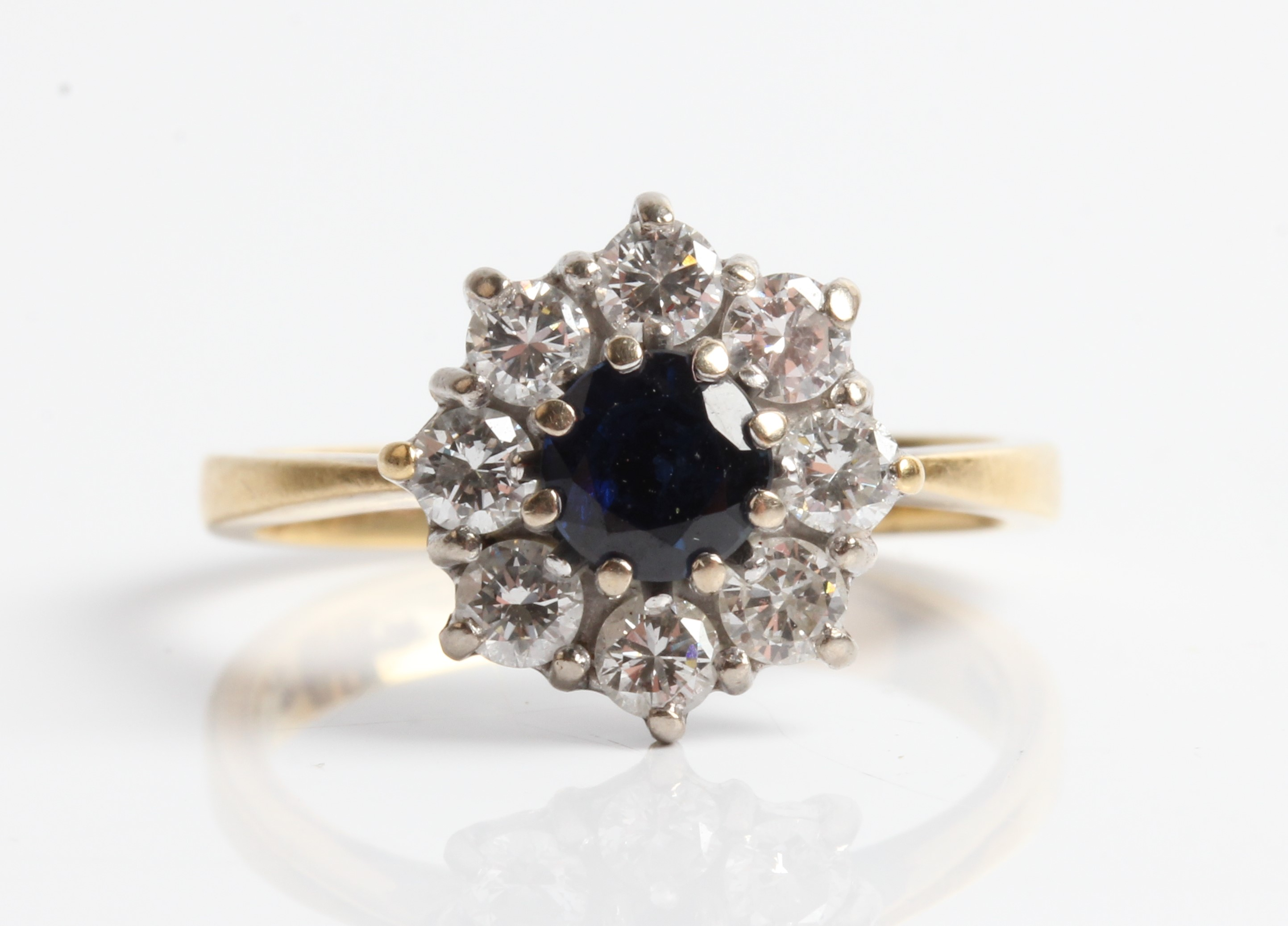 A hallmarked 18ct yellow gold (rubbed) sapphire and diamond cluster ring, set with a central round