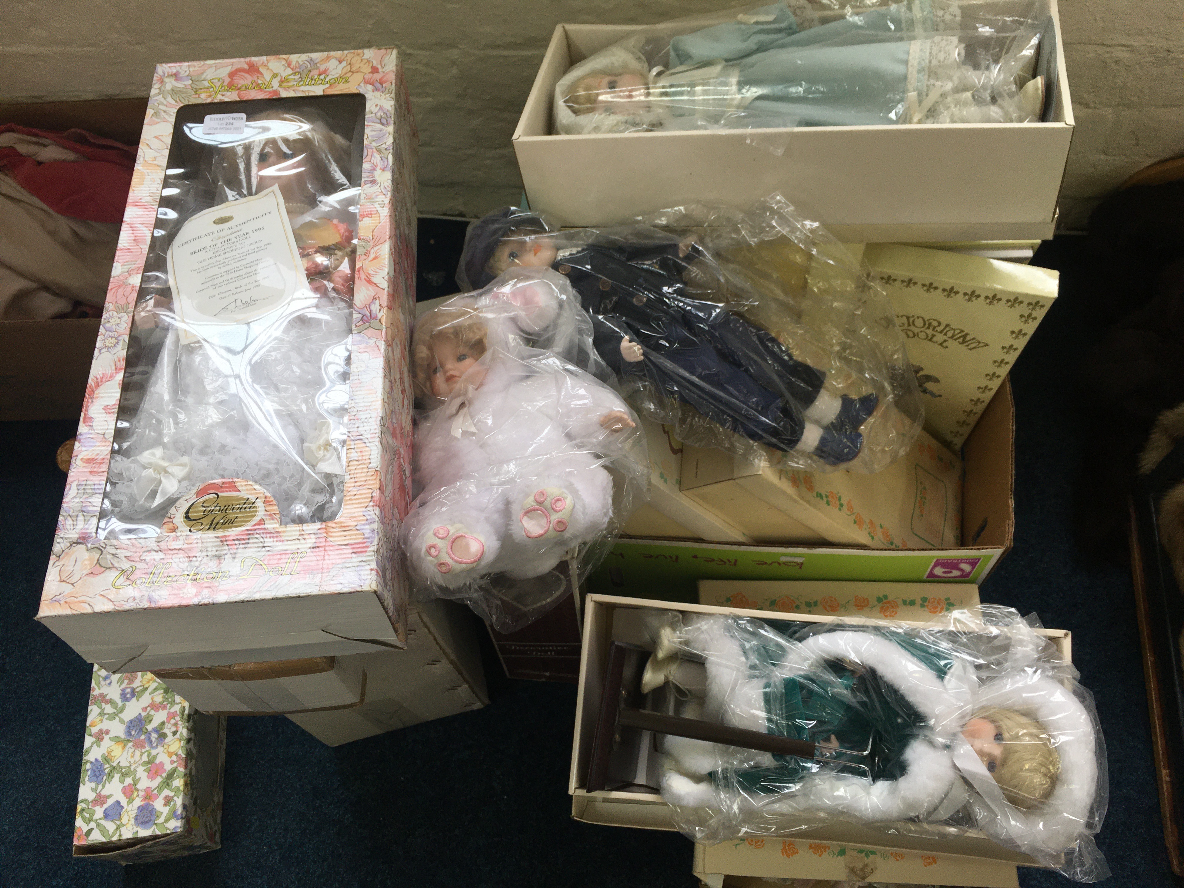 A selection of eighteen various porcelain dolls, in various sizes and designs, including PMC musical