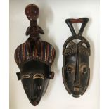 Two West African tribal face masks, one blue and red painted details topped with female, one