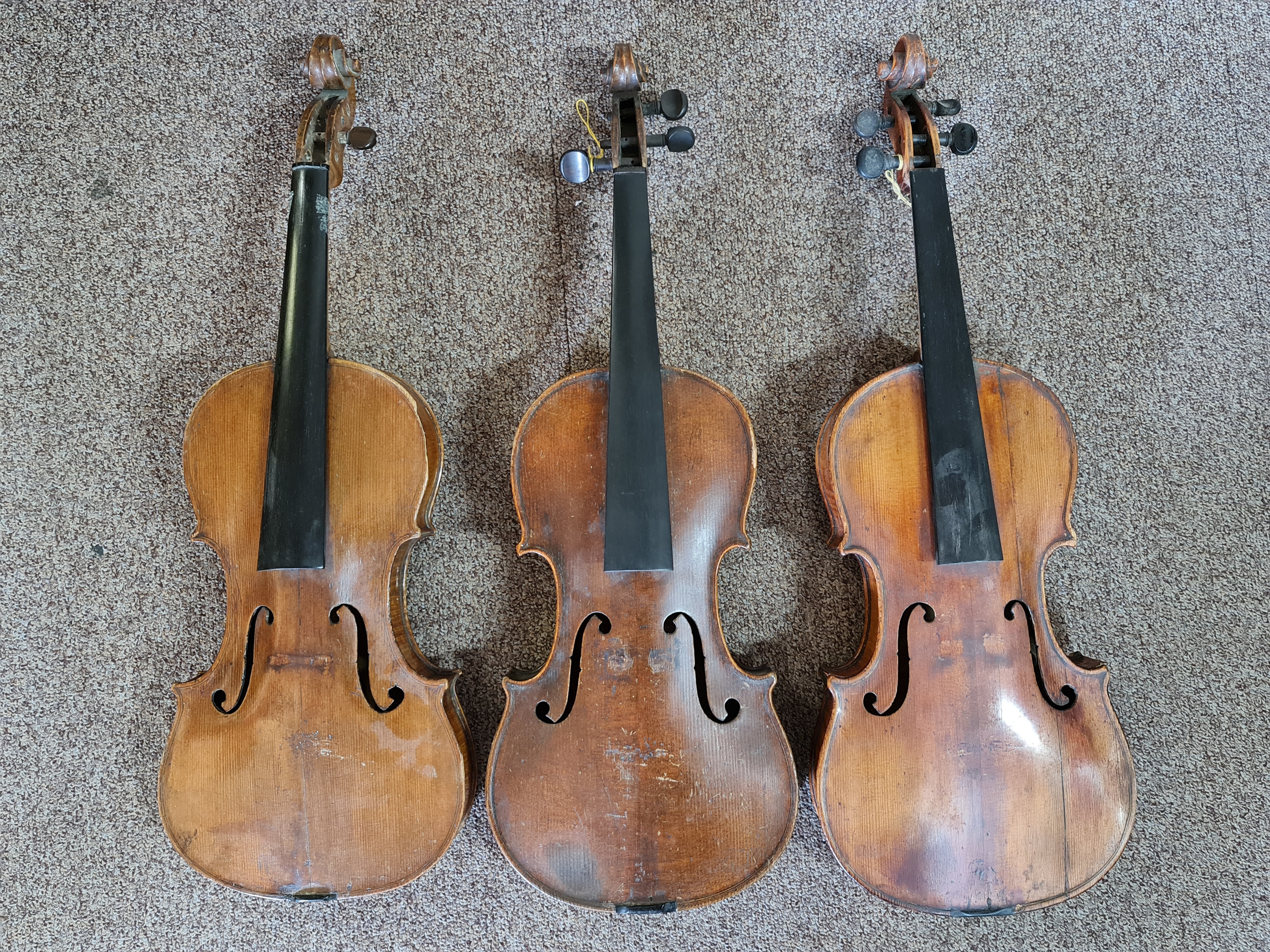 Three violins, one inscribed 'Hope' to back, one with front detached, no strings or cases.